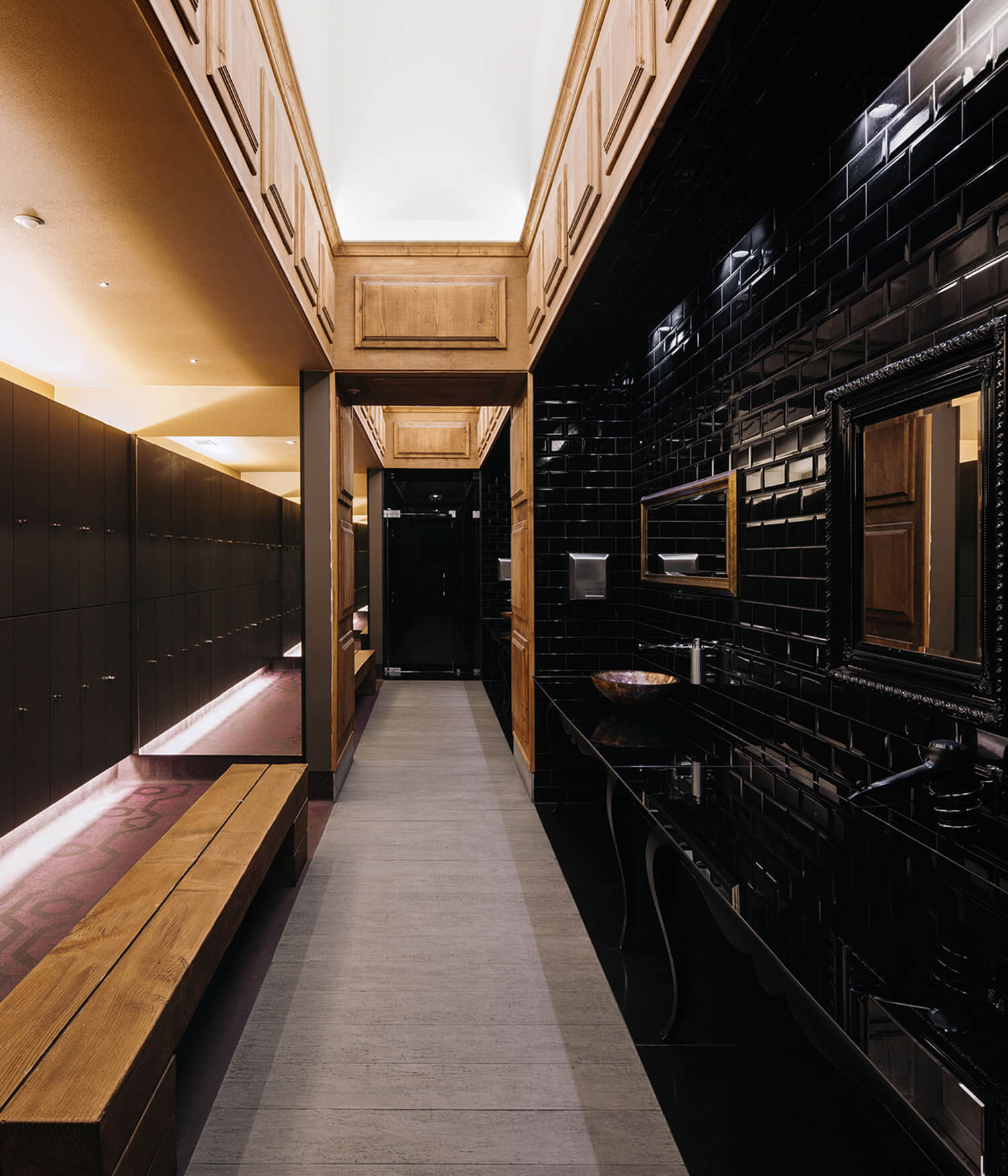 Perspective of the corridor contiguous to the lavatories and dryers, on the right, and to the dressing area of mirrored walls and backlit lockers, on the left.