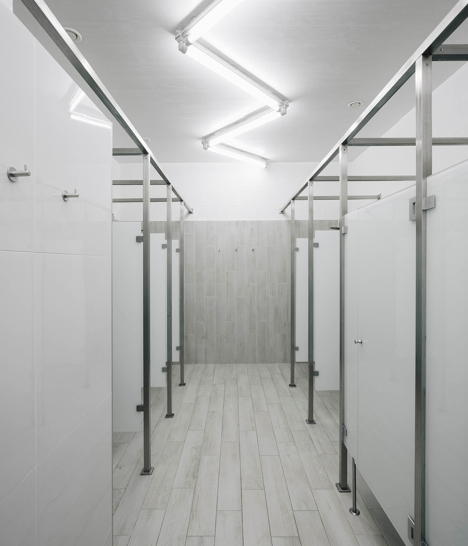 Such as in the male dressing room, one can have the same monochromatic feeling in the female dressing room. Instead of black, the glass door is in white color.