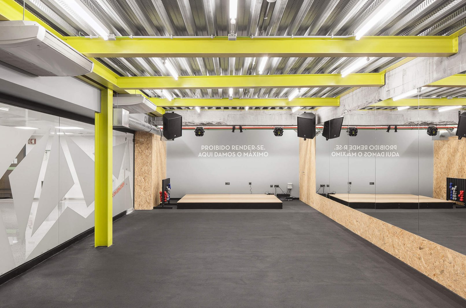 The beam structure that supports the ceiling was painted in yellow in order to give a distinct identity to the fitness studio compared to the other spaces.